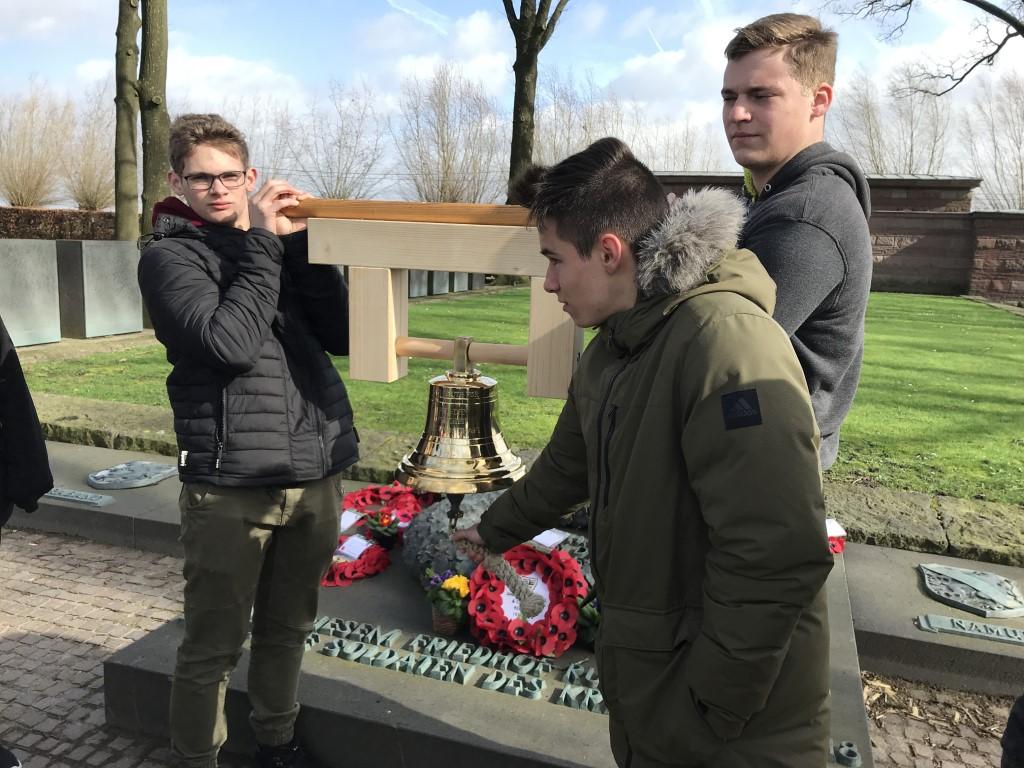 Luis Ermert und Lukas Reihs tragen die Glocke. Leon Hein läutet zum Gedenken in Langemark (Belgien) (Mittel)
